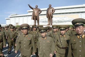 北朝鮮の故金日成主席の死去から25年を迎え、金主席(左)と故金正日総書記の銅像が立つ「万寿台の丘」へ献花に訪れた軍人ら=8日、平壌(共同)