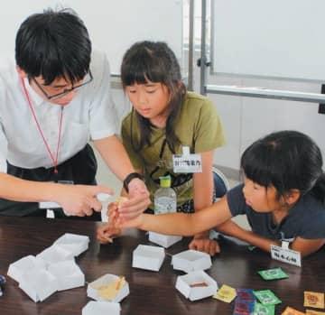 双国校の生徒と試食をしながら意見を出し合う児童ら=国東市の竹田津小