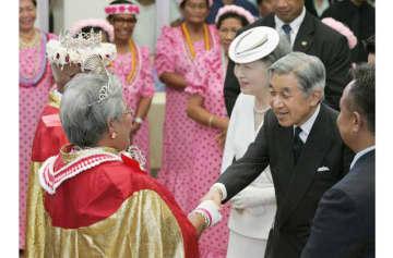 サイパンの敬老センターを訪問され、現地の伝統的な衣装のお年寄りと握手する天皇陛下と皇后さま=28日午後(共同)