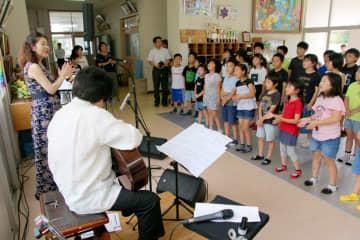 山口修さんのギターと純子さん(左)の歌声に合わせ合唱する児童=西海市立雪浦小