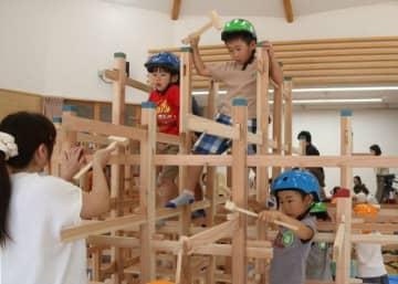 木づちでくさびを打ち込み、ジャングルジムを組み立てる園児たち
