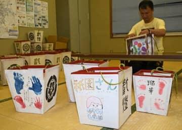 地域の子どもたちの手形や足形、イラストが貼られている小献灯(9日、和歌山県田辺市新庄町で)