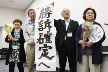 ハンセン病家族訴訟で首相が控訴しないことを表明。垂れ幕を手にポーズを取る原告団。中央右は、林力団長、左端は原田信子さん=9日午後、国会