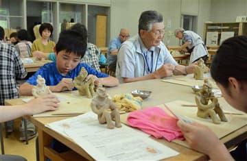 見本を確認しながら合掌土偶を制作する参加者ら