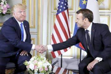 握手するトランプ米大統領(左)とフランスのマクロン大統領=6月6日、フランス北西部カン(ロイター=共同)