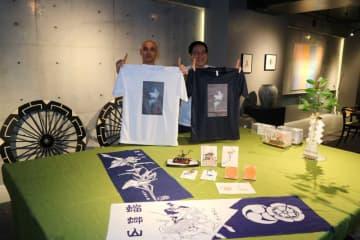 新デザインの手拭いやTシャツを紹介する今井さん(左)と蟷螂山保存会の村林利高会長(京都市中京区)