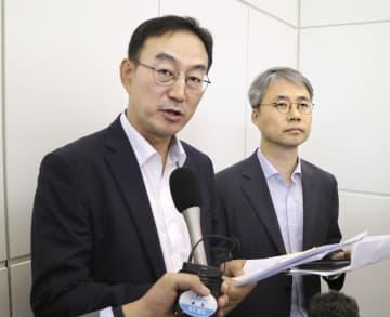 羽田空港で出発前に取材に応じる韓国政府当局者=13日午前