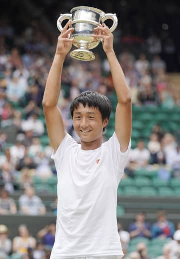 テニスのウィンブルドン・ジュニア選手権の男子シングルスで日本勢初優勝を果たし、カップを掲げて喜ぶ望月慎太郎=14日、ウィンブルドン(共同)