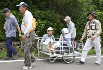 避難訓練で高齢者をリヤカーに乗せ、避難所まで搬送する住民たち=16日午前、新潟県柏崎市