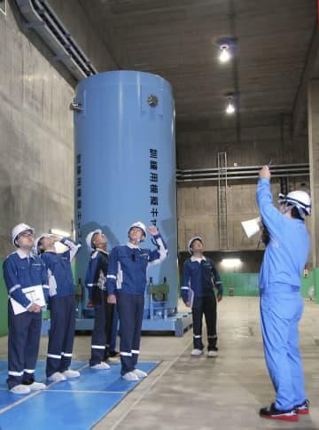 原発から出た使用済み核燃料の中間貯蔵施設を現地調査する原子力規制委の山中伸介委員(右から3人目)=18日午前、青森県むつ市