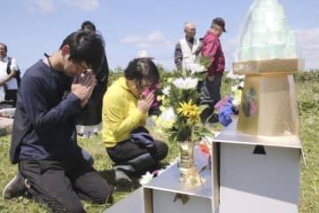 択捉島のペケンリタ墓地での慰霊式で、手を合わせる「北方領土墓参」団員=19日(同行記者団撮影)
