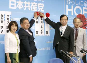 当確者の名前にバラを付ける共産党の志位委員長(中央右)と小池書記局長(同左)=21日午後10時19分、東京都渋谷区の党本部