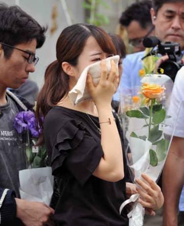 献花に訪れ、ハンカチを口に当てて涙ぐむ女性(21日午前11時55分、京都市伏見区)