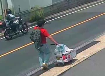ガソリン携行缶の箱などを積んだ台車を押す、青葉容疑者とみられる男(17日午前11時20分、京都府宇治市槙島町)