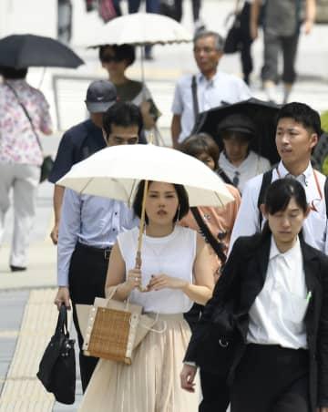 強い日差しの中、日傘を差して歩く女性ら=24日午前、大阪市