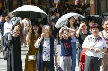 強い日差しの中、信号待ちする人たち=24日午後、大阪市