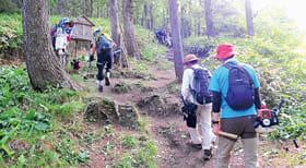 登山道の草刈りに向かう関係者ら(提供写真)