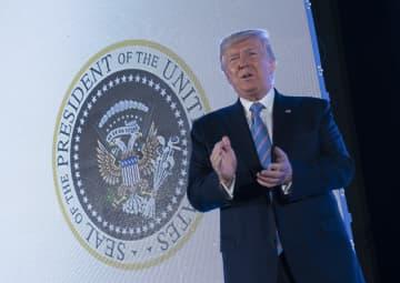 23日、ワシントンの会合に出席したトランプ米大統領。背後に紋章が見える(UPI=共同)