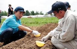 トウモロコシの種を植えるたけだバーベキューさん(左)=播磨農業高校