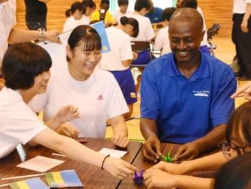折り鶴作りを通じて交流を深めるルワンダの選手団と安代中の生徒