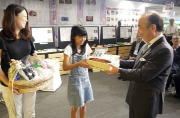 青果物や水産物の詰め合わせを受け取る畑中さん(中央)=京都市下京区、京の食文化ミュージアム・あじわい館