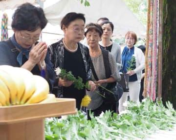 原爆被害者の慰霊碑に献花し、手を合わせる参列者たち(京都市東山区・霊山観音)