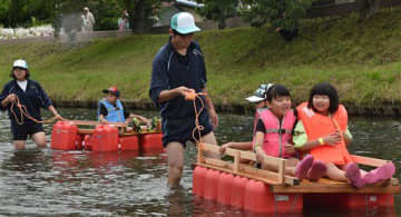 いかだに乗って川下りを楽しむ子どもたち
