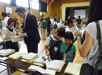 タイムカプセルから出てきた文集などを見る同窓生や子どもたち=君津市立坂畑小学校
