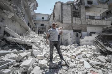 シリアのアサド政権軍とロシア軍の空爆で破壊された建物を示す男性=27日、シリア北西部イドリブ県(ゲッティ=共同)