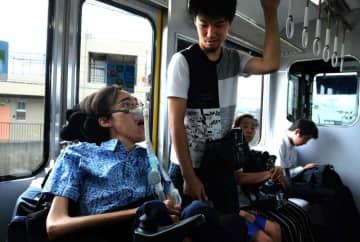 ヘルパーと一緒に電車で通勤するライスチョウ・ノアさん(京都市)