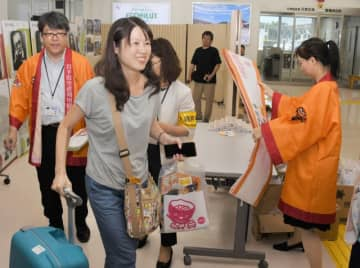 就航1周年の記念品を手に笑顔で岩手入りした台湾からの観光客(左から2人目)=31日、花巻市・花巻空港
