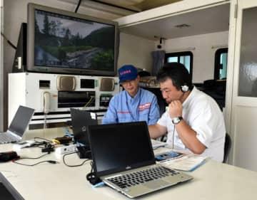 雫石町役場前の対策本部車内で、テレビ電話を通じて被災状況を東北地方整備局に伝える参加者