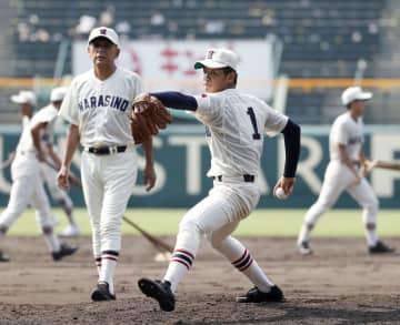 甲子園で投球練習する習志野・飯塚(1)。左は小林監督