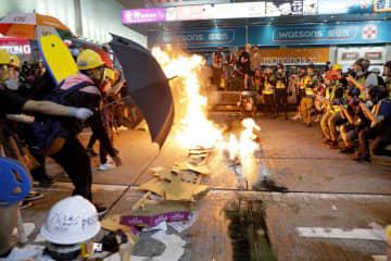 段ボールを燃やして警官隊と対峙する香港のデモ隊=3日(AP=共同)