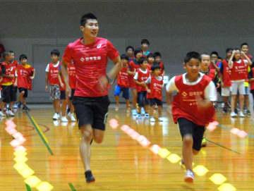 子供たちと楽しく走る桐生選手(大阪市・市立港スポーツセンター)