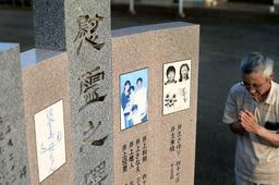 濁流にのまれ、9人が犠牲になった現場の慰霊碑。亡くなった子どもらをよく知る近所の山本孝行さんが10年前を思い出し、手を合わせる=兵庫県佐用町本郷(撮影・小林良多)