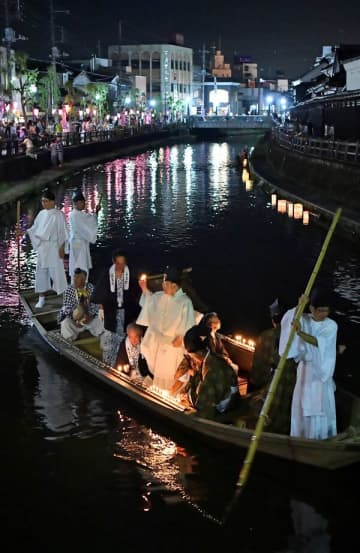 ろうそくをともして巴波川を行き交う舟=4日午後8時25分、栃木市湊町