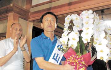 3選を果たし、支持者から花束を受け取った小山氏(右)=4日午後9時25分ごろ、宮城県川崎町の事務所