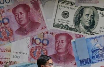 中国人民元など各国通貨の写真を配した香港の外貨両替店=6月(AP=共同)