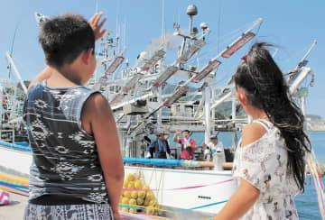 手を振りながら出港する船を見送る子どもたち