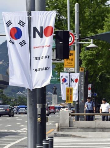 批判が殺到し、撤去されることが決まった、日本製品の不買運動などを呼び掛ける旗(右側)=6日、ソウル中心部(共同)