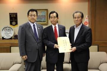 佐賀県議会の桃崎議長(右)に基本方針と協力要請書を手渡す山本委員長(中央)