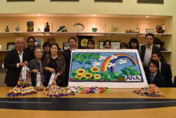 モザイクアートと千羽鶴を贈ったANAテレマートの社員となごみ荘入居者ら=長崎原爆資料館