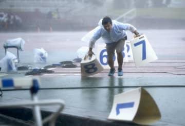 台風9号による強風と大雨で全国高校総体の陸上競技が中断し、備品を片付ける係員=8日午前11時21分、沖縄県沖縄市