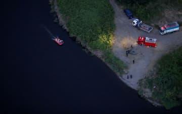 男子高校生2人が流され行方不明となった利根川の現場周辺を捜索する捜査員ら=8日午後6時50分、群馬県大泉町(共同通信社ヘリから)
