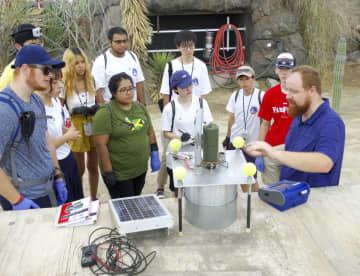 風速に応じて砂嵐の規模がどう変わるのか調べるための実験装置(中央)について説明を聞く大学生ら=8日、米アリゾナ州(共同)