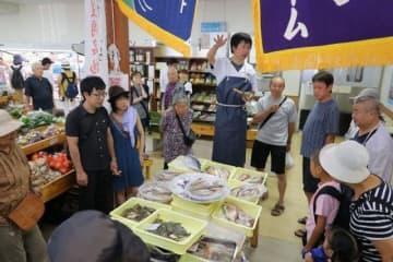 買い物客が詰め掛けた模擬せり市。競り人を務める寺田さん(中央)の掛け声が響き、新鮮な水産物が次々と競り落とされた