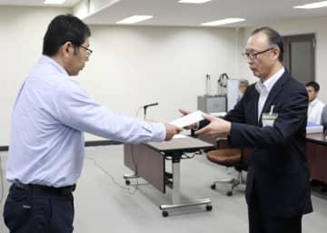 中2自殺問題で第三者委の委員長(左)から調査報告書を受け取る仙台市教委の佐々木洋教育長=9日午後、仙台市