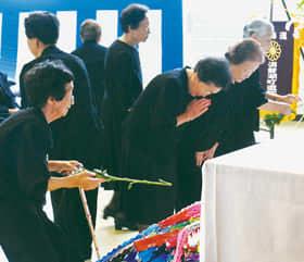 祭壇に白菊を備え手を合わせる参列者