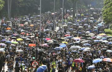 香港の新界地区でデモ行進する人たち=10日(共同)